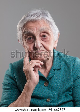 Elderly woman smiling with a flower in her ear in a studio shot. - stock photo