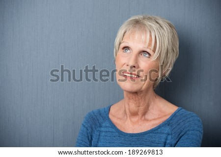 Elderly woman standing daydreaming or reminiscing looking up into the air with a faraway expression, head and shoulders against a blue background with copyspace - stock photo