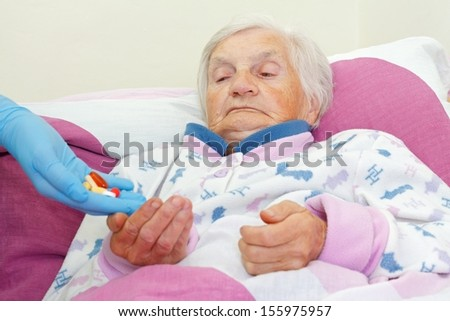 Elderly woman takes pills from a nurse - stock photo