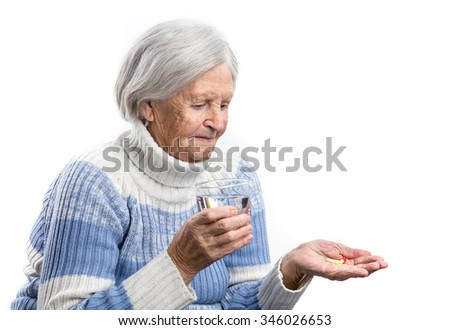 Elderly woman taking her medication over white  - stock photo