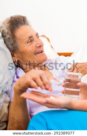 Elderly woman taking pills with glass of water. - stock photo