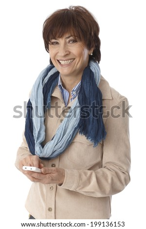 Elderly woman using mobilephone, smiling, looking at camera. - stock photo