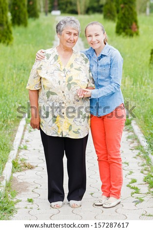 Elderly woman walk with her daughter in the park - stock photo