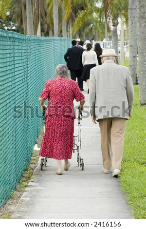 elderly woman walking down a path holding onto a walker next to husband - stock photo