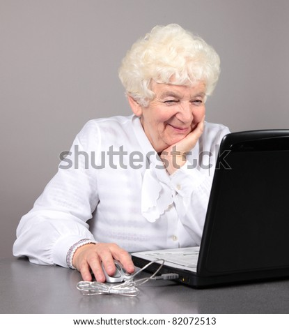 elderly woman with computer - stock photo
