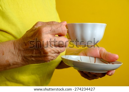 Elderly woman with cup of tea - stock photo