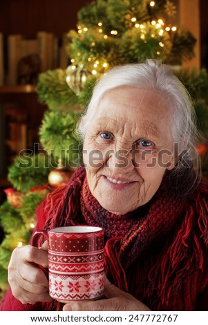 Elderly woman with cup of tea  near christmas tree - stock photo