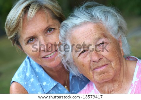 Elderly woman with her daughter. Focus on the senior woman. - stock photo