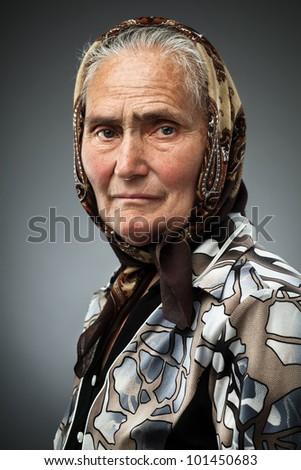 Elderly woman with kerchief, studio portrait - stock photo