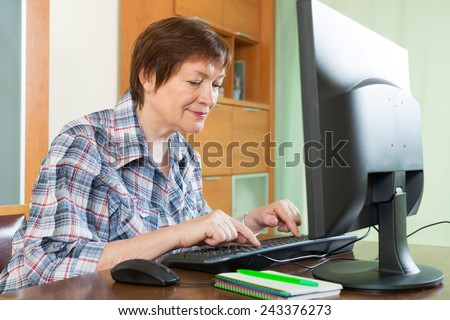Elderly woman working with personal computer in office interior - stock photo