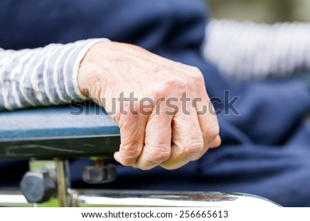 Elderly womans hand resting on a wheelchair - stock photo