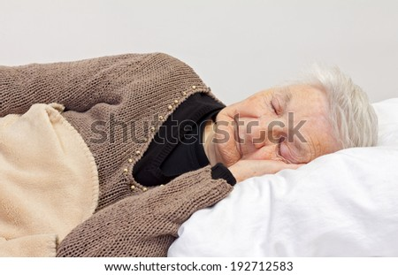 Elderly wrinkled woman laying in the bed - stock photo