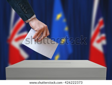Election or referendum in Great Britain. Voter holds envelope in hand above vote ballot. British and European Union flags in background. - stock photo