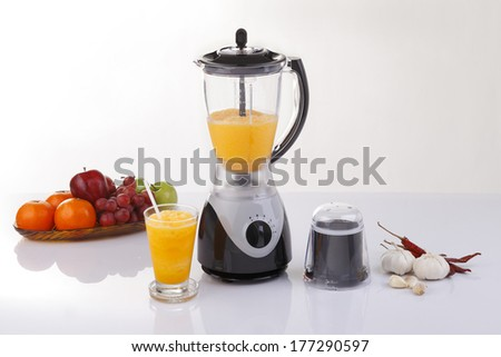 Electric blender with fruits and orange juice - stock photo