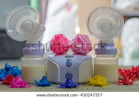 Electric breast pump to increase milk supply for breastfeeding mother and feeding bottle with breastmilk  - stock photo