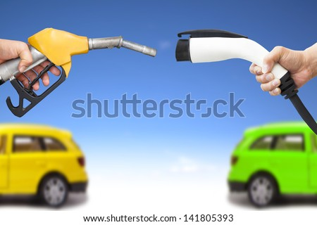 electric car and gasoline car concept. hand holding gas pump and power connector for refuel - stock photo