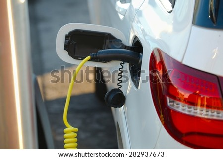 Electric car at a charging station - stock photo