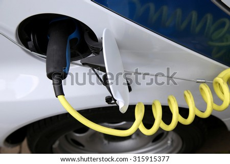 Electric car being charged at the station, close up of the power supply plugged - stock photo