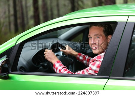 Electric car driver - green energy biofuel concept. Male behind wheel. Man driving new vehicle in cheerful in nature forest. Young male driver looking at camera with arm raised cheering. - stock photo