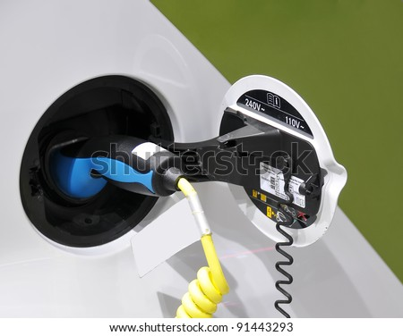 Electric Car - plugged in for charging - stock photo
