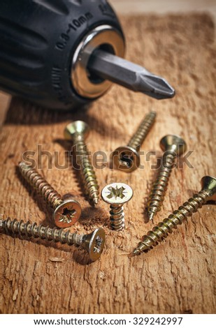 Electric drill and screws on wooden background - stock photo