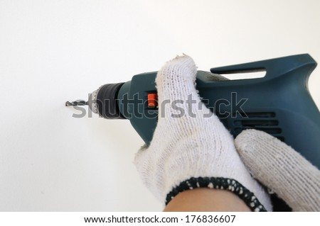 Electric drill touching wall, action concept. - stock photo