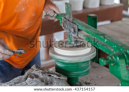 electric drive rotating wheel for jiggering or throwing production process for craft and industrial ceramic with a plaster mold and metal jiggering arm - stock photo