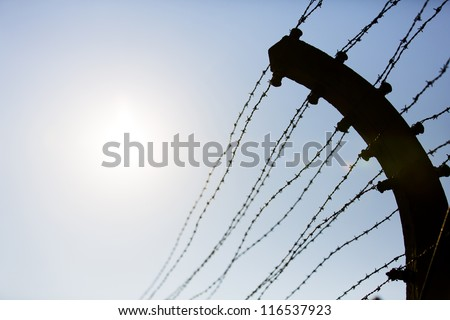 Electric fence in Auschwitz I, a former Nazi extermination camp in Oswiecim, Poland. It was the biggest nazi concentration camp in Europe. - stock photo