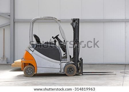 Electric Forklift Truck in Distribution Warehouse - stock photo