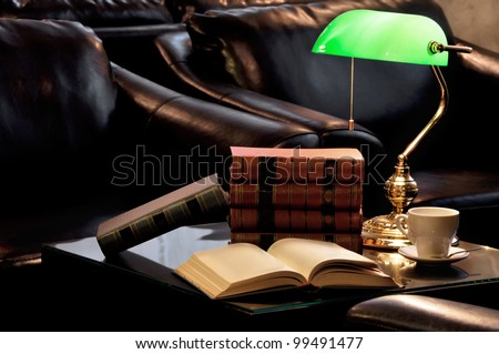 Electric green table lamp and books with leather armchair and cup of tea - stock photo