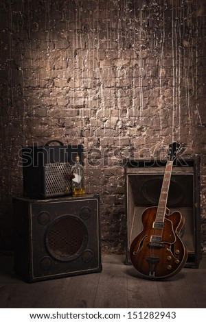 Electric guitar and old amplifier on a grunge wall background  - stock photo