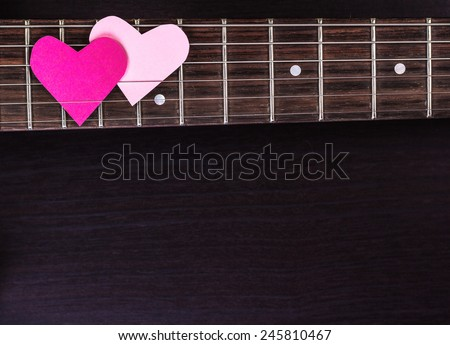 Electric guitar deck with paper hearts on dark background. Above view. - stock photo