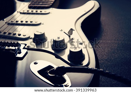 Electric guitar. Detail, focus on the cable plug. Shallow depth of field. Music, learning how to play the guitar and abstract concept - stock photo