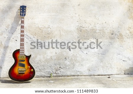 electric guitar in front of a vintage wall - stock photo