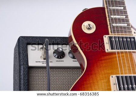 Electric guitar leaning with old amplifier and patch cable - stock photo