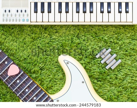electric guitar , music keyboard / piano & pitch tuning pipe on green - stock photo