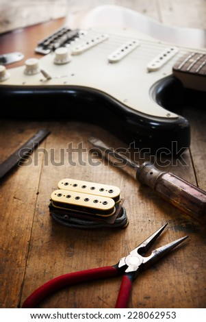 Electric guitar repair. Electric guitar and double coil pickup and tools. - stock photo