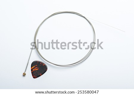 Electric guitar string with mediator on white surface - stock photo