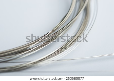 Electric guitar strings on white surface - stock photo