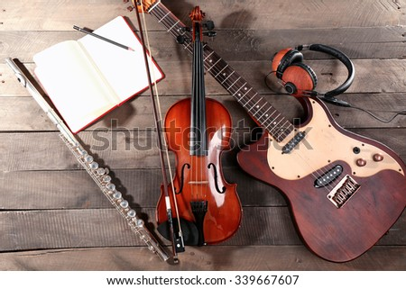Electric guitar, violin, soprano saxophone, headphones and book on wooden background - stock photo