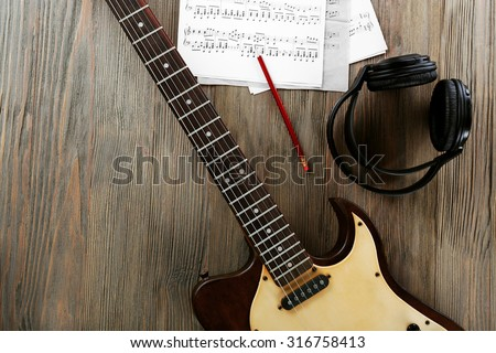 Electric guitar with headphones and music notes on wooden table close up - stock photo