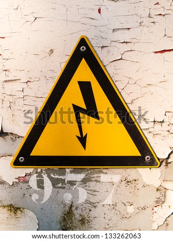 Electric hazardous area warning sign on a wall with cracked paint - stock photo