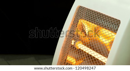 Electric heater with halogen coils close up. Dark copy spice - stock photo