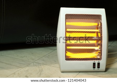 Electric heater with halogen coils. Heater on marble slabs - stock photo