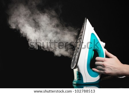 Electric iron with steam on black - stock photo