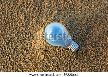 Electric lamp on the beach which contained a small world inside. - stock photo