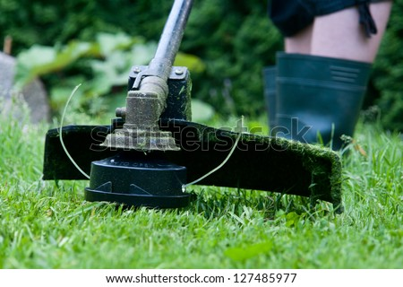 Electric lawn trimmer on an oblique grass. - stock photo