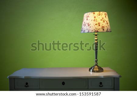 electric lighting lamp on white table with emerald green cement wall background - stock photo