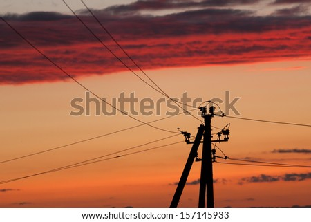 Electric line against colorful sky at sunset  - stock photo