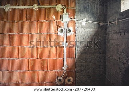 electric lines construction at new estate, electricity pipes and brick walls under construction - stock photo